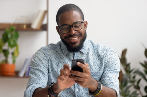 Happy african american businessman using phone mobile apps at workplace