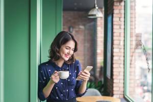 Beautiful cute asian young businesswoman in the cafe, using mobi